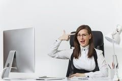 Mooie bedrijfsvrouw in kostuum en glazen die bij computer met documenten in licht bureau werken stock foto's