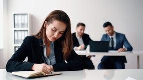 Mooie bedrijfsvrouwenzitting in bureau en het maken van nota's stock videobeelden