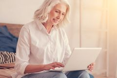 Mooie bejaarde dame die aan laptop thuis werken stock foto's