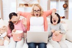 Mooie bejaarde grootmoeder het letten op griezelfilm op laptop met haar kleinkinderen samen stock fotografie