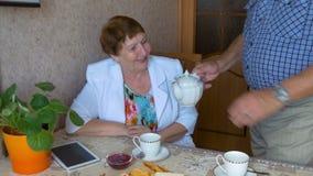 Mooie bejaarde paar het drinken thee bij de lijst stock footage