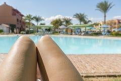 mooie benen in het meisje tegen de achtergrond van water Mooie lange slanke vrouwelijke benen van een meisje met knie?n en heupen stock fotografie