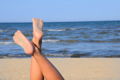Mooie benen op het strand op blauwe hemel Stock Foto