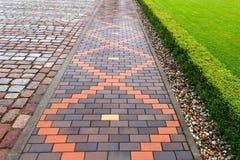 Mooie bestrating van rode en bruine clinker baksteen Lopende weg Royalty-vrije Stock Afbeeldingen