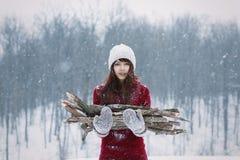 Mooie bevroren meisjesholding firewoods op gang door het bosmeisje van de de wintersneeuw met mittend en brandhout Warm en firewo stock fotografie