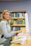 Mooie bibliothecaris die in de bibliotheek werken stock afbeeldingen