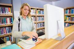 Mooie bibliothecaris die in de bibliotheek werken stock foto's