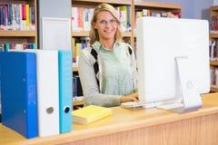 Mooie bibliothecaris die in de bibliotheek werken stock fotografie