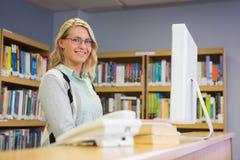 Mooie bibliothecaris die in de bibliotheek werken stock afbeelding