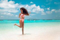 Mooie bikinivrouw die met lang haar op tropisch strand springen Vrij het slanke meisje stellen op exotisch eiland in turkooise oc royalty-vrije stock afbeeldingen