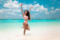 Mooie bikinivrouw die met lang haar op tropisch strand springen Vrij het slanke meisje stellen op exotisch eiland in turkooise oc stock foto