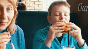 Mooie blauw-eyed jongenstiener die hamburger in een snel voedselrestaurant eten Mond van een jongen die een hamburger en een mamm stock video