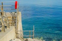 Mooie blauwe oceaan, een zonnige deel van de promenade met reddingsboei, Stock Afbeeldingen