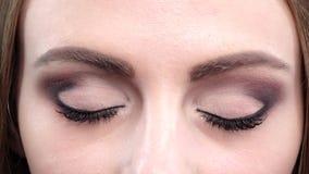 Mooie blauwe ogen, knipoogje, heldere make-up Sluit omhoog stock video