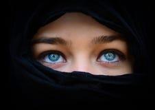 Mooie blauwe vrouwenogen achter zwarte sjaal die omhoog eruit zien Stock Foto's