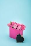 Mooie bloeiende roze rozen in decoratieve document zak en leeg die hartsymbool op blauw wordt geïsoleerd Stock Afbeeldingen