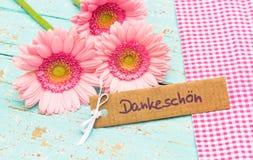 Mooie bloemen en kaart met Duits woord, Dankeschoen, middelendank stock foto