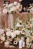 Mooie bloemensamenstellingen bij de huwelijkslijst van witte wonden, rozen en transparante kandelaars stock fotografie