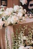 Mooie bloemensamenstellingen op de huwelijkslijst van witte Ranunculus, rozen en bloemen stock afbeelding