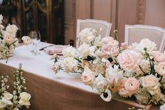 Mooie bloemensamenstellingen op de huwelijkslijst van witte wonden, rozen en bloemen Naast de uitstekende stoelen en stock foto