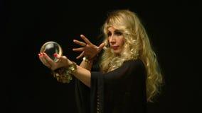 Mooie blonde astroloogvrouw die door kristallen bol kijken stock videobeelden