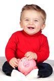 Mooie blonde baby met een piggy-bank Stock Afbeeldingen