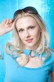 Mooie blonde in blauw met zonnebril Royalty-vrije Stock Afbeeldingen