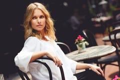 Mooie blonde damezitting in openluchtkoffie op zonnige dag Stock Foto's