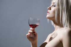 Mooie blonde die een glas rode wijn houdt Stock Afbeelding