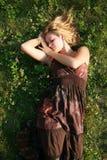 Mooie blonde die op het gras ligt Royalty-vrije Stock Foto