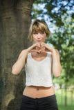 Mooie blonde jonge vrouw die hartteken doen met Stock Fotografie