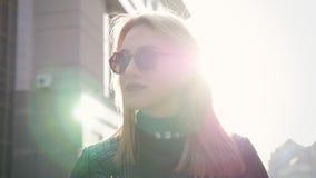 Mooie blonde jonge vrouw die op de straat lopen stock footage