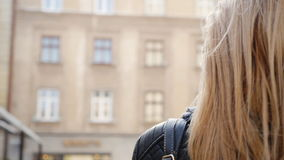 Mooie blonde jonge vrouw die op de straat lopen stock videobeelden