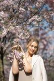 Mooie blonde jonge vrouw die in Sakura Cherry Blossom-park in de Lente van aard en vrije tijd genieten tijdens haar die reizen stock foto