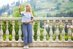 Mooie blonde jonge vrouw die selfie in een park nemen stock foto's