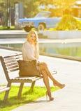 Mooie blonde meisjeszitting op een bank en het spreken op de telefoon Het modelmeisje bekijkt de camera royalty-vrije stock foto's