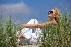 Mooie blonde meisjeszitting op een zand in duinen Stock Foto's
