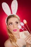 Mooie blonde vrouw als Paashaas met konijnoren op rode achtergrond, studioschot Jonge dame die drie gekleurde eieren houden Stock Afbeeldingen