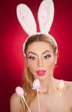 Mooie blonde vrouw als Paashaas met konijnoren op rode achtergrond, studioschot Jonge dame die drie gekleurde eieren houden Stock Foto
