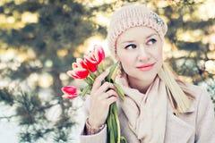 Mooie blonde vrouw in de winter biege kleren met bloemen Openluchtportrate met onduidelijk beeld royalty-vrije stock afbeelding