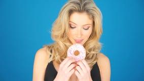 Mooie blonde vrouw die een grote doughnut eten stock videobeelden