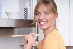 Mooie blonde vrouw die een smakelijke maaltijd kookt Stock Foto's
