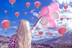 Mooie blonde vrouw die en zich een mooi landschap en bergen bevinden bekijken En hij houdt roze ballen in zijn hand royalty-vrije stock foto's