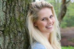 Mooie blonde vrouw die in het bos glimlachen stock fotografie