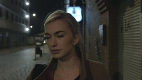 Mooie blonde vrouw die in laag alleen in openlucht bij nacht lopen korrel Langzame Motie stock videobeelden