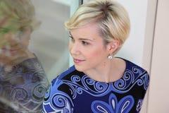 Mooie blonde vrouw die in venster wordt weerspiegeld stock afbeelding
