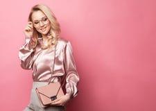Mooie blonde vrouw in een blouse en broek die glazen dragen, die handtas houden Royalty-vrije Stock Foto