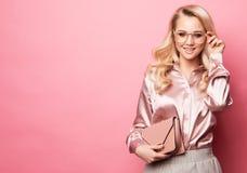 Mooie blonde vrouw in een blouse en broek die glazen dragen, die handtas houden Stock Afbeeldingen