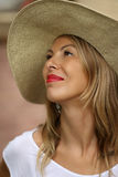 Mooie blonde vrouw in een hoed die omhoog met rode lippen in een witte t-shirt kijken royalty-vrije stock foto's
