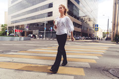 Mooie blonde vrouw met koffie gaan kruisend de weg Royalty-vrije Stock Afbeeldingen